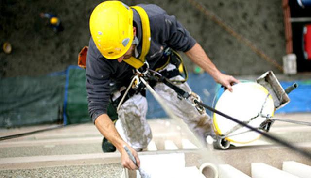 альпинист очищает фасад здания